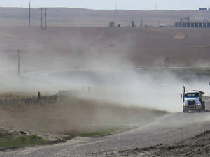 Photo - A cloud of dust trails a semitrailer on an unpaved road in Williston, N.D., on Saturday, May 3, 2014. Unpaved roads are essential to North Dakota's oil industry, but controlling the dust they produce can be difficult and expensive. (AP Photo/Josh Wood)