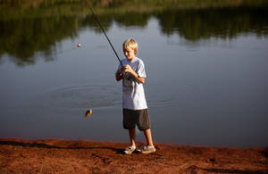 Photo - Austin Ellefson, 13, catches a fish during a clinic Thursday at Arcadia Lake. Fishing clinics are held from 6:30 to 8:30 p.m. each Thursday this month.