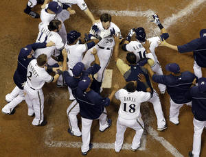 Photo - Milwaukee Brewers' Jonathan Lucroy is mobbed by teammates after hitting a walkoff two-run home run during the ninth inning of a baseball game against the Cincinnati Reds, Friday, Aug. 16, 2013, in Milwaukee. The Brewers won 7-6. (AP Photo/Morry Gash)