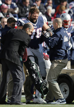 Photo - New England Patriots tackle Sebastian Vollmer is tended after an injury in the second quarter of an NFL football game against the Miami Dolphins on Sunday, Oct. 27, 2013, in Foxborough, Mass. (AP Photo/Michael Dwyer)