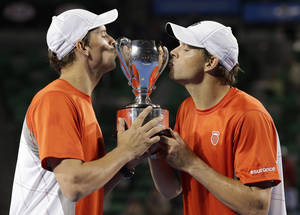 photo - Bob, left, and Mike Bryan of the US kiss their trophy after defeating Robin Haase and Igor Sijsling of the Netherlands in the men's doubles final at the Australian Open tennis championship in Melbourne, Australia, Sunday, Jan. 27, 2013.(AP Photo/Andy Wong)