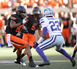 Photo - Oklahoma State wide receiver Tracy Moore, left, holds up his hand to fend off Kansas State's Tre Flowers, right, during the second half of an NCAA football game in Stillwater, Okla., Saturday, Oct. 5, 2013. (AP Photo/Brody Schmidt)