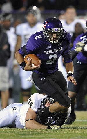 Photo -   Vanderbilt's Jimmy Stewart (54) tries to grab the ankles of Northwestern's Kain Colter (2) who runs upfield during the first half of an NCAA college football game on Saturday, Sept. 8, 2012, in Evanston, Ill. (AP Photo/Jim Prisching)