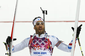 Photo - France's Martin Fourcade celebrates winning the gold during the men's biathlon 12.5k pursuit, at the 2014 Winter Olympics, Monday, Feb. 10, 2014, in Krasnaya Polyana, Russia. (AP Photo/Felipe Dana)