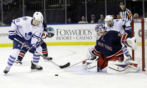 Photo - New York Rangers goalie Cam Talbot (33) stops a shot on the goal by Toronto Maple Leafs' James van Riemsdyk (21) during the first period of an NHL hockey game, Monday, Dec. 23, 2013, in New York. (AP Photo/Frank Franklin II)