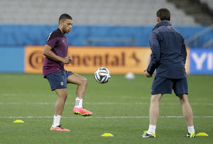 Photo - England national soccer player Alex Oxlade-Chamberlain, left, trains away from the rest of the squad whilst continuing to recover from a knee injury during a training session for the 2014 soccer World Cup at Itaquerao Stadium in Sao Paulo, Brazil, Wednesday, June 18, 2014.  Uruguay play England in group D of the 2014 soccer World Cup at the stadium on Thursday.  (AP Photo/Matt Dunham)