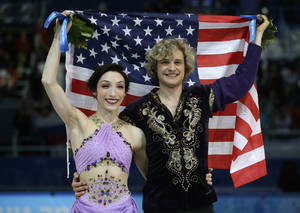 Photo - Meryl Davis and Charlie White of the United States pose for photographers with the U.S. flag after placing first in the ice dance free dance figure skating finals at the Iceberg Skating Palace during the 2014 Winter Olympics, Monday, Feb. 17, 2014, in Sochi, Russia. (AP Photo/Darron Cummings)