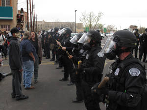 Photo - Albuquerque police face off with protesters Sunday, March 30, 2014, in downtown Albuquerque, N.M. during a protest against recent police shootings. Hundreds of protesters marched past riot police in Albuquerque on Sunday, days after a YouTube video emerged threatening retaliation for a recent deadly police shooting. The video, which bore the logo of the computer hacking collective Anonymous, warned of a cyberattack on city websites and called for the protest march. (AP Photo/Russell Contreras)