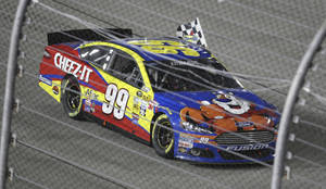 Photo - Carl Edwards takes the checkered flag around the track as he celebrates winning the NASCAR Sprint Cup Series auto race at Richmond International Raceway in Richmond, Va., Saturday, Sept. 7, 2013.  (AP Photo/Jason Hirschfeld)