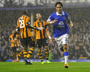 Photo - Everton's Steven Pienaar celebrates in the rain after scoring his side's second goal against Hull City during their Barclays Premier League match at Goodison Park, Liverpool, Saturday Oct. 19, 2013. (AP Photro / Dave Howarth/PA) UNITED KINGDOM OUT  NO SALES  NO ARCHIVES