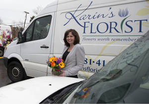 Photo - In this Friday, Feb. 21, 2014, photo, Maris Angolia, president of Karin's Florist, stands with two of Karin's Florist's delivery vehicles, a 2006 Scion xB, front, and a 2011 Mercedes-Benz Sprinter, behind, outside Karin's Florist, in Vienna, Va. (AP Photo/Carolyn Kaster)