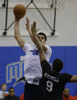 Photo - Oklahoma City Thunder's Steven Adams, left, takes a shot over Detroit Pistons' Tony Mitchell (9) during an NBA summer league basketball game, Tuesday, July 9, 2013, in Orlando, Fla. (AP Photo/John Raoux) ORG XMIT: DOA112