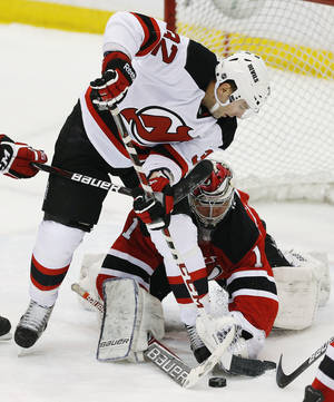 Photo - New Jersey Devils' Mathiew Darche, top, tries to score against Devils goalie Johan Hedberg (1), of Sweden, during an NHL hockey scrimmage, Wednesday, Jan. 16, 2013, in Newark, N.J. (AP Photo/Julio Cortez)