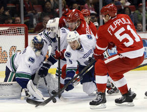 Photo - Vancouver Canucks goalie Roberto Luongo, left, and defenseman Christopher Tanev (8) defend the goal as Detroit Red Wings center Valtteri Filppula (51), of Finland, and left wing Justin Abdelkader, top, try to score a goal in the second period of an NHL hockey game Sunday, Feb. 24, 2013, in Detroit. (AP Photo/Duane Burleson)