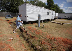 Photo - Bobby Miller crosses a ditch from his camp site at the Hand Up Ministry in Oklahoma City, Wednesday, July 25, 2012.  Photo by Garett Fisbeck, The Oklahoman Archives