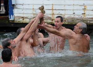 Photo - Swimmers celebrate together after Lukas Kokinis from Greece, second right, retrieved a wooden cross which was thrown into the waters by Ecumenical Patriarch Bartholomew I during a ceremony to bless the water at the Golden Horn in Istanbul, Turkey, Sunday, Jan. 6, 2013. The traditional ceremony marks the Epithany in Istanbul, Turkey, when an Orthodox priest throws a wooden cross into the water and swimmers race to be the first to retrieve it. (AP Photo)