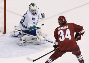 Photo - Vancouver Canucks' Eddie Lack (31) makes a save on a shot by Phoenix Coyotes' Tim Kennedy (34) during the second period of an NHL hockey game on Thursday, Jan. 16, 2014, in Glendale, Ariz. (AP Photo/Ross D. Franklin)