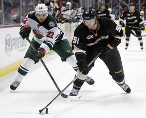 Photo - Anaheim Ducks defenseman Alex Grant (51) battles Minnesota Wild right wing Nino Niederreiter (22), of Switzerland for the puck in the first period of an NHL hockey game Wednesday, Dec. 11, 2013 in Anaheim, Calif.  (AP Photo/Alex Gallardo)