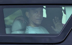 Photo - President Barack Obama waves from the window of his motorcade vehicle as he returns from a workout at Marine Corp Base Hawaii, Monday, Dec. 24, 2012, in Kailua, Hawaii. The president and the first family are in Hawaii for a family holiday vacation. (AP Photo/Carolyn Kaster)