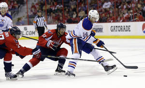 Photo - Edmonton Oilers center Jordan Eberle (14) tries to get away from Washington Capitals defenseman Karl Alzner (27) and center Jay Beagle (83) in the second period of an NHL hockey game, Monday, Oct. 14, 2013, in Washington . (AP Photo/Alex Brandon)