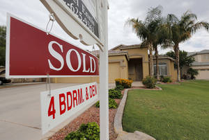 Photo - In this Monday, Aug. 26, 2013 photo, a used home is listed as sold, in Gilbert, Ariz.  Freddie Mac reports on mortgage rates for this week Thursday Oct. 17, 2013. (AP Photo/Matt York)