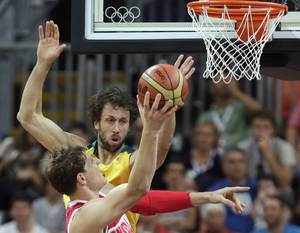 Photo -   Australia's Matt Nielsen reaches to block as Russia's Timofey Mozgov drives to the basket during a men's basketball game at the 2012 Summer Olympics, Monday, Aug. 6, 2012, in London. (AP Photo/Charles Krupa)