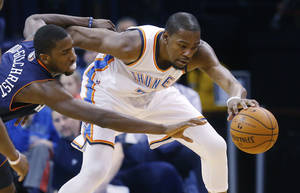 Photo - Oklahoma City Thunder forward Kevin Durant (35) keeps the ball away from Charlotte Bobcats forward Michael Kidd-Gilchrist (14) during the first quarter of an NBA basketball game in Oklahoma City, Sunday, March 2, 2014. (AP Photo/Sue Ogrocki)