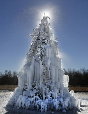 Photo - The sun shines from behind the top of an ice sculpture Monday along NE 23 in Choctaw. A hose sprays water from the top of a metal tree frame to make the sculpture in frigid weather. Photo By Steve Gooch, The Oklahoman <strong>Steve Gooch</strong>