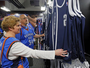 Photo - Bethany Brown and Cliff Brown look at the new alternate Thunder uniforms before an NBA basketball game between the Detroit Pistons and the Oklahoma City Thunder at the Chesapeake Energy Arena in Oklahoma City, Friday, Nov. 9, 2012. Photo by Nate Billings, The Oklahoman