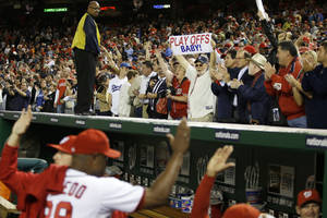 Photo -   Washington Nationals players high-five as fans celebrate their 4-1 win against the Los Angeles Dodgers to clinch a playoff spot after their baseball game at Nationals Park in Washington, Thursday, Sept. 20, 2012. (AP Photo/Jacquelyn Martin)