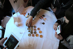 Photo - FILE - In this Feb. 12, 2014 file photo, attendees of the Inside Bitcoins conference in Berlin examine Bitcoin buttons. The website of major Bitcoin exchange Mt. Gox is offline amid reports it suffered a debilitating theft of the virtual currency, and the URL of the Tokyo-based outfit returns a blank page on Tuesday, Feb. 25, 2014. (AP Photo/Frank Jordans, File)
