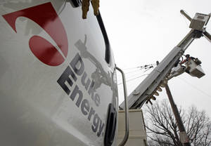 Photo - FILE - In this Feb. 14, 2012 file photo, Duke Energy employees work on power lines in Charlotte, N.C. Duke Energy Corp. reports quarterly earnings on Tuesday, Feb. 18, 2014. (AP Photo/Chuck Burton, File)