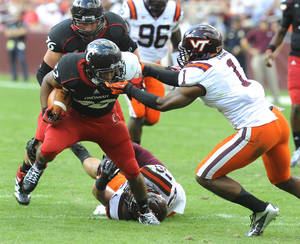 photo -   Cincinnati running back George Winn has his face mask grabbed by Virginia Tech cornerback Antone Exum (1) during the first half of an NCAA college football game, Saturday, Sept. 29, 2012, in Landover, Md. (AP Photo/Richard A. Lipski)