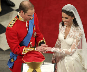 Photo - Kate Middleton looks as happy as a princess on her wedding day as Prince William places the ring on her finger. AP Photo