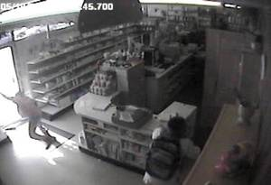 photo - In this image from a 2009 surveillance recording, robber Jevontai Ingram flees out the door of the Reliable Discount Pharmacy in south Oklahoma City while a scond robber, Antwun Parker, is shot as he pulls on a mask. <strong></strong>