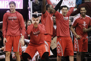 Photo - From left, Houston Rockets' Chandler Parsons, Jeremy Lin, Patrick Patterson, Carlos Delfino and Greg Smith celebrate a teammate's 3-pointer against the Utah Jazz in the fourth quarter of their NBA basketball game, Monday, Jan. 28, 2013, in Salt Lake City. The Rockets won 125-80. (AP Photo/Rick Bowmer)