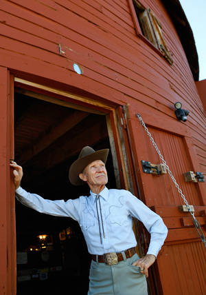 Photo - Sam Gillaspy steps outside of a door on the east side of the historic Round Barn in Arcadia to look up at construction of the billboard on Oct. 14, 2010. <strong>JIM BECKEL - THE OKLAHOMAN</strong>