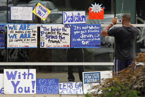 Photo -   A Penn State University football player stops to take pictures of signs hung outside the Lasch Football Building by supporters of the team after the team's morning workout in State College, Pa., Tuesday, July 31, 2012. (AP Photo/Gene J. Puskar)