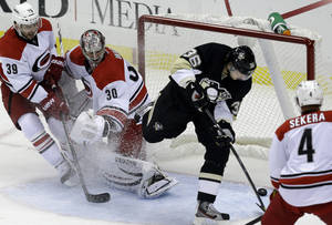 Photo - Pittsburgh Penguins' Jussi Jokinen (36) backhands the puck behind Carolina Hurricanes goalie Cam Ward (30) and Patrick Dwyer (39) for a first-period goal during an NHL hockey game in Pittsburgh, Tuesday, Oct. 8, 2013. (AP Photo/Gene J. Puskar)
