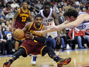 Photo -   Cleveland Cavaliers' Kyrie Irving (2) turns the ball over as he falls in front of Philadelphia 76ers' Spencer Hawes (00) and Jrue Holiday (11) during the second half of an NBA basketball game on Sunday, Nov. 18, 2012, in Philadelphia. The 76ers won 86-79. (AP Photo/Michael Perez)