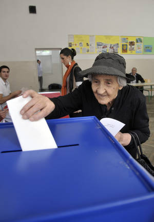 Photo -   A woman casts her ballot at a polling station in downtown Podgorica, Montenegro, Sunday, Oct. 14, 2012. Djukanovic is again a favorite to win weekend parliamentary elections in the tiny Balkan nation seeking membership in the European Union. (AP Photo/Risto Bozovic)
