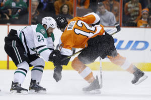Photo - Dallas Stars' Jordie Benn, left, collides with Philadelphia Flyers' Michael Raffl, of Austria, during the first period of an NHL hockey game, Thursday, March 20, 2014, in Philadelphia. Benn was penalized for hooking on the play. (AP Photo/Matt Slocum)