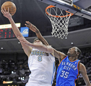 Photo - Denver forward Danilo Gallinari, left, puts up a shot against Thunder forward Kevin Durant during the Nuggets' win Monday. AP PHOTO