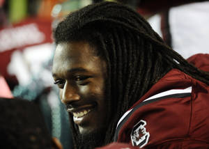 Photo - South Carolina defensive end Jadeveon Clowney smiles as he sits on the bench during the first half of an NCAA college football game against Kentucky, Saturday, Oct. 5, 2013, in Columbia, S.C. (AP Photo/Rainier Ehrhardt)