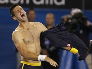 photo - Serbia's Novak Djokovic rips his shirt off as he celebrates his fourth round win over Switzerland's Stanislas Wawrinka at the Australian Open tennis championship in Melbourne, Australia, Monday, Jan. 21, 2013. (AP Photo/Dita Alangkara)