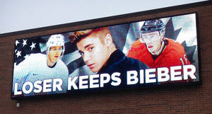 Photo - In this photo provided by Command Transportation, an electronic billboard displays pop star Justin Bieber, center, sandwiched by Chicago Blackhawks stars Patrick Kane, left, and Jonathan Toews outside the Skokie, Ill., based freight company. Kane, who plays for Team USA and Toews for Team Canada, played against each other in a men's semifinal ice hockey game at the 2014 Winter Olympics, Friday, Feb. 21, 2014. Canada won 1-0 to advance to the gold medal game. (AP Photo/Command Transportation)