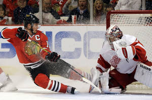 Photo - Detroit Red Wings goalie Jimmy Howard, right, saves a shot by Chicago Blackhawks' Jonathan Toews, left, during the second period of Game 5 of the NHL hockey Stanley Cup playoffs Western Conference semifinals in Chicago, Saturday, May 25, 2013. (AP Photo/Nam Y. Huh)