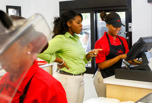 Photo - In this July 31, 2014 photo, Quamisha Nelson, owner and operator of the Smoothie King in Jacksonville, N.C., center, works alongside Latasia White, 15, as she rings up a customer's order at the drive-thru. The government reports on state unemployment rates for July on Monday, Aug. 18, 2014. (AP Photo/The Jacksonville Daily News, John Sudbrink)