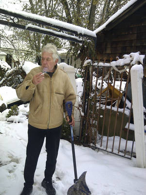 "Photo - <p>Vladimir Repnin, 63, emerges from his powerless home with snow shovel in hand and a cigarette, Thursday, Nov. 8, 2012, in New Dorp Beach, in the Staten Island borough of New York. Reflecting his isolation from the outside world he asked; ""Who won? Obama?"" (AP Photo/Tom Hays)</p>"