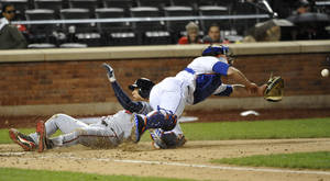Photo - Atlanta Braves' Andrelton Simmons, left, scores at home plate as New York Mets catcher Anthony Recker misses ball in the fifth inning of the second baseball game at Citi Field, Saturday, May 25, 2013, in New York. (AP Photo/Kathy Kmonicek)